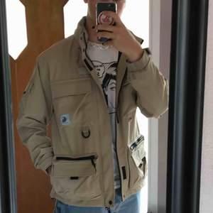 Carhartt jacka med fickor och infvikbar luva. Använd fåtal gånger och är i bra skick. Tror den även kan vara vattentät men är inte 100% på det.