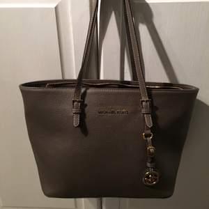 MK väska. Liten och brun/grå. Guldiga detaljer. 250 kr. Tar swish!