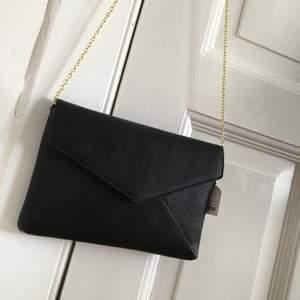 Svart väska i skinnimitation med guldkedja från Accent. Aldrig använd. Frakt tillkommer.