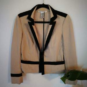 A classic jacket with a really good fit. It's comfortable and could be worn with a range of things, whether it be more official events or casually with jeans. The color is beige with black detailing.