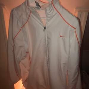 En vit sportjacka från Nike med orangea ränder. Jätte cool och väldigt bra skick. Frakt TILLKOMMER!