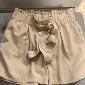 Kostym shorts med snöre och detalj runt midjan. Färgen beige.