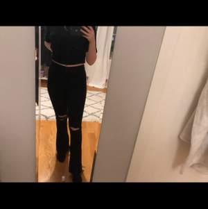 Svarta bootcut jeans med slitningar vid knäna. Bra skick