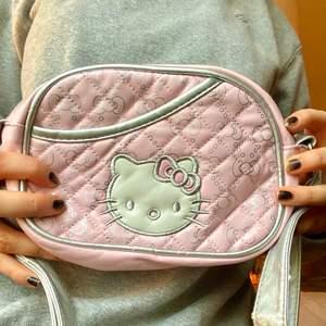 Justerbar Hello Kitty handväska! Ljusrosa med hello Kittys ansikte på ena sidan och ett justerbart silvrigt band! Köpt second hand, använt skick (små slitningar här och där på axelbandet). Frakt 22kr