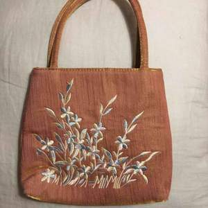 Superfin väska i lite guldskimrande material med fin brodyr i pastellfärger💘 Köpt secondhand i nyskick. Säljer då den inte kommer till användning tyvärr. Möts eller fraktar!