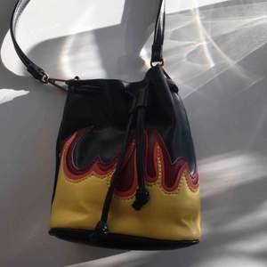 väska med flammor i läderimitation från bikbok. oanvänd!