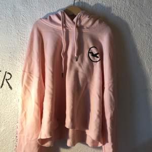 Rosa croppar hollister hoodie, tryck på huva och tryck på ärmarna.  Avklippt nederkant dok inte av migsjälv (köpare står för frakt)