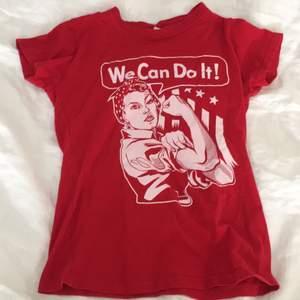 """En röd t-shitt med ett tryck där det står """"we can do it"""" som är för kvinnornas rättighet. ❤️ väldeligt bra skick. Köparen står för frakten🥰"""