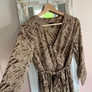 Helt ny klänning från Vero Moda i storlek M. Beige bakgrund med bruna samt orangea detaljer. Knäppning från bröstet med samt knutna midja. Mycket lätt tyg som passar bra på sommaren. Aldrig använd. Säljer pga fel storlek för mig