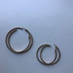 Två par guldiga örhängen med diamantliknande stenar. De stora är aldrig använda och de små är endast använda 1 gång. Båda paren är inkluderade i priset. Frakt inkluderat i priset!