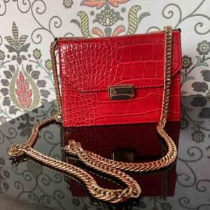 Oerhört fin röd väska, i fake ormskin, helt oanvänd och väldigt rymlig.