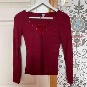 Röd tröja med snörning vid bröstet.