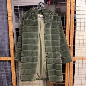"""En jättefin faux fur jacka med luva från White Icy i storlek Small. Jackan är i jättebra skick och i """"Moss"""" grön färg."""