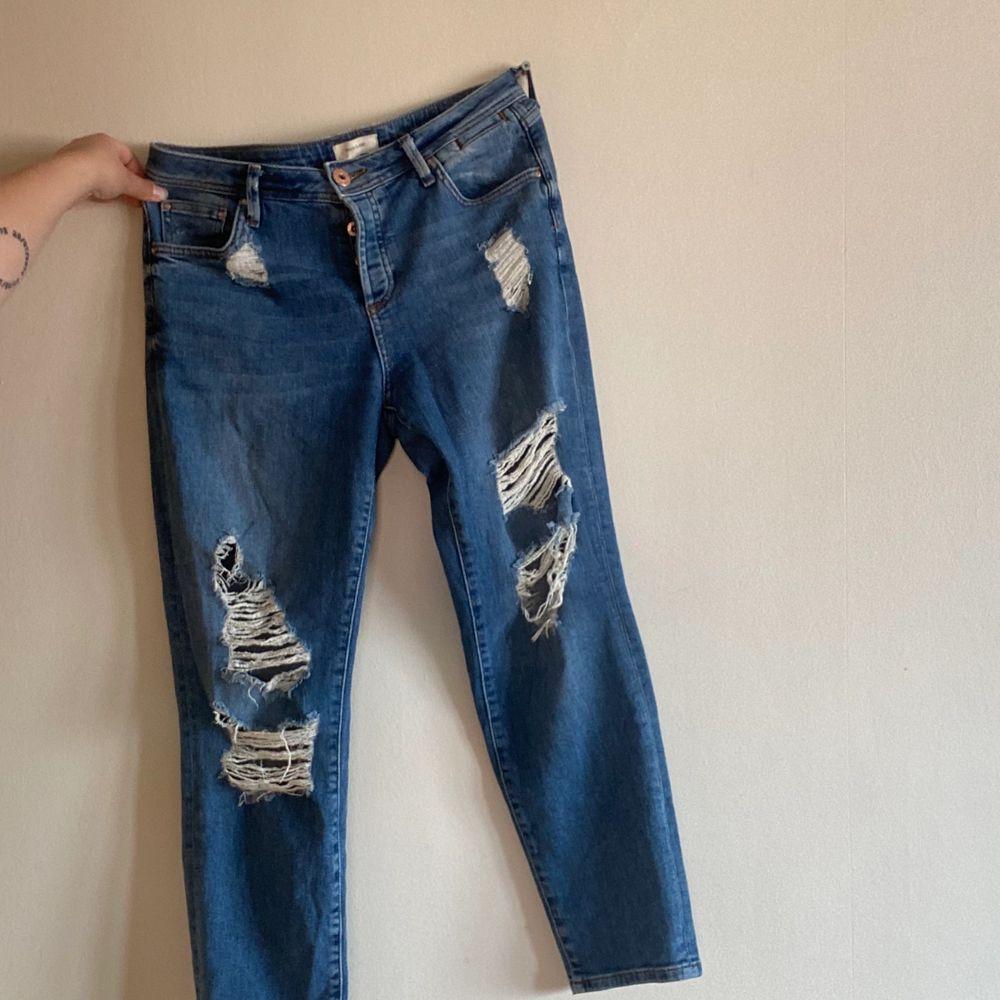 Slitna jeans från River Island. Knappar istället för dragkedja. Storlek 12 vilket motsvarar strl 40. Inköpta för över 500:-.. Jeans & Byxor.