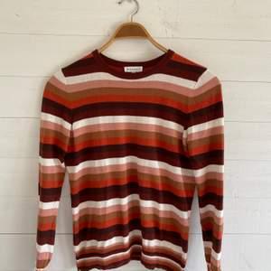 Randig stickad tröja med färgerna orange, brun och beige. Mycket bra skick! Originalpris: 300 kr