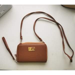 Liten brun väska, axelbandet och det lilla bandet går att ta av så fungerar också som en plånbok, den har några mindre skador på baksidan (se bild 3) 40kr + frakt 22kr