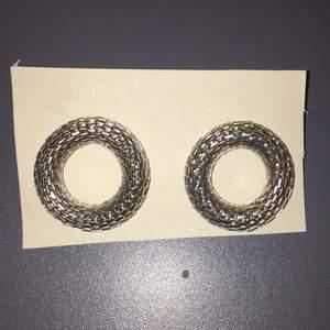 Ett par silvriga örhängen från Gina tricot. Aldrig använda