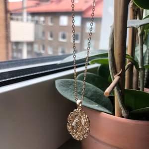 Ett guldigt halsband med ett motiv som liknar jungfru Maria. Halsbandet är oanvänt, frakten kostar 11kr oavsett hur många smycken man köper!!