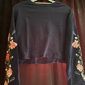 Super gullig kroppad sweatshirt med blommor på armarna. Är marinblå med vida armar. Jätte fint skick.