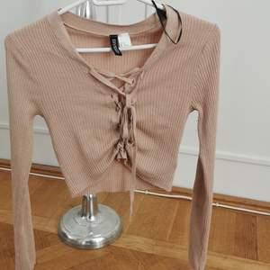 Jättefin ribbad beige tröja med snörimg, man kan knyta om den så den blir längre eller kortare 😊 testad men säljer för att den fick mig ej att se blek ut haha så köpte vit istället :) är xs men är väldigt stretchig