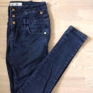 Mörkblå jeans från Topshop med hög midja och guldiga knappar.