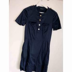 Mörkblå klänning med guldknappar ifrån märket Stockholm, använd 1 gång. 90 kr inklusive frakt. Storlek 34 men passar absolut en 36a