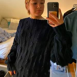 Marinblå mönsterstickad tröja som inte kommer till användning. OBS: det är spegeln som är smutsig.