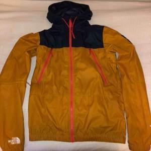 North Face regn jacka. Den är orange där nere och blå lite högre upp och på luvan, faktiskt ganska varm men också  perfekt för att sporta i. Använd bara några få gånger. Köpte originellt för 1,300. Dm-a för mer info:)