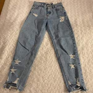 Slitna jeans från Pull&Bear i storlek 32 💙💙 Jeansen har mom-fit och har fina slitningar i form av stjärnor ⭐️ Dem är i mycket fint skick och är använda max 1 gång! Samfraktar gärna med andra plagg och betalning sker via Swish <33