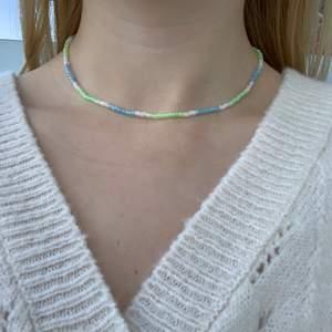 Blått, grönt & vitt pärlhalsband med små pärlor🤍🦋💚🍭💕💙🐢 halsbandet försluts med lås och tråden är elastisk