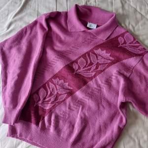 En rosa stickad tröja med rosor på, har också krage vilket är najs. Säljer då den är lite kort i armarna på mig som är 181 cm:) lite stickig men funkar finfint om man har en tunn tröja under som jag har på bilden. Så fin men kommer inte till användning😔