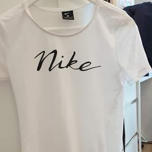 Vit t-shirt från NIKE. Storlek s men passar alla storlekar beroende på hur man vill att den ska sitta. Materialet där fram är i