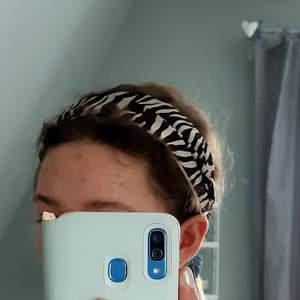 Mjukt hårband i glansigt tyg. Zebraränder i brunt och beige-vit. Sitter bra och funkar både för att få håret ur vägen och som en snygg accessoar. I gott skick trots att den inte är så ny. Älskar den, men säljer då den inte riktigt är min stil längre. ❤