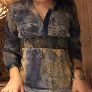 liknar blusar som var trendiga på 00-talet. hade passat väldigt bra med bootcut jeans. fint motiv på blusen