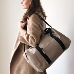 Beige color travel bag made by Rains. Spacious, waterproof, and super stylish bag. Measurements: 51x26x21.
