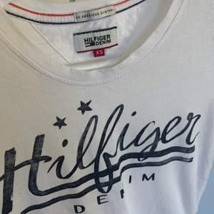 Säljer denna snygga T-shirt från Tommy Hilfiger då den inte kommer till användning.. strl xs. Fint skick! Pris + frakt.