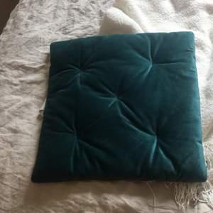 Grön stolskudde i sammetliknande material. Icke använd.
