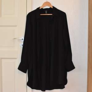 En lång svart jättefin skjorta som kan användas både till vardags och till finare tillställningar. Skulle kunna passa M-L. Den är från Lindex.  Nypris var kring 300-400 kr om jag minns rätt. Inte använd många gånger, den är i fint skick.