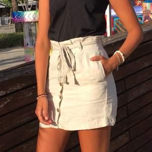 Jätte snygg kjol i linntyg från h&m. Knyte upptil och knappar på framsidan. Väldigt bra skick. Köpare står för frakten.