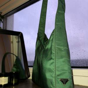 """A Rare Prada shoulder bag in an asymmetrical green nylon style. This designer handbag features an asymmetrical body with a single shoulder strap and a Prada emblem near the base. The interior is tagged, """"Prada Milano Made in Italy"""" beneath a zippered sidewall pocket in the signature Prada lining. A """"63"""" tag marks the lower interior corner.  Condition  Good"""