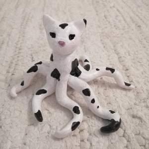 Handgjord kattfigur med tentakel-armar. Gjord i lera, målad med akryl och lackad. Ca 7 cm hög. Finns i Hökarängen eller fraktas.