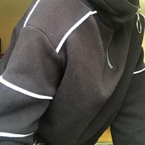 Svart hoodie med vita streck och dragkedja. Mag längd ungefär.