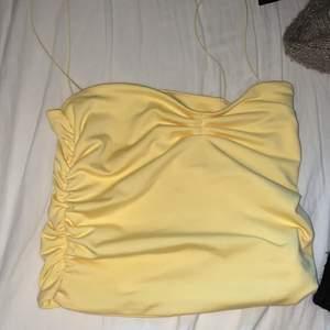 """Säljer detta gula linne med """"scrunch"""" på sidorna som gör att den formar kroppen super snyggt. Det är helt nytt och bara testat. Storlek Xs"""