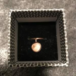 Ring i äkta silver med en rosa Sten från Edblad. Oanvänd. Ringen är färgad i rosé guld. Storlek 17 Mm men är öppen och där av skjuster bar. Köparen står för frakten.