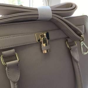Don Donna handväska i bra skick. Handväskan är i färgen beige och har gulddetaljer och axelband. Vill du ha mer bilder på väskan är det bara att fråga :) Ordinarie pris: 435 kr