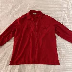 Röd lång skjorta i strl L/XXL från Cappucini Framfickor och knappr finns. Aldrig använd.