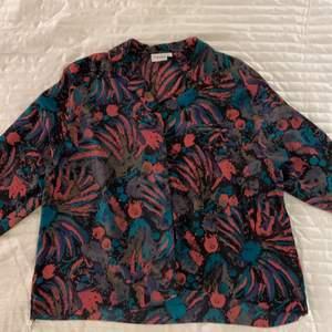 Färgglad mönstrad skjorta i 100 % polyester. Skönt silkesliknande material. Mönstrad i färgerna rosa, turkos, brun och svart. Har knappar och en krage.