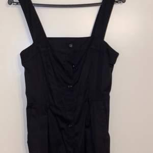 En svart klänning med knappar från h&m i storlek 38.