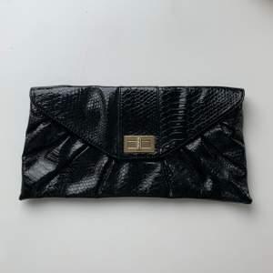 Svart handväska/clutch i ormskinn - större irl än vad den ser ut på bild! Bra skick, knappt använt ☺️☺️ Frakt tillkommer!