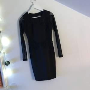 En svart klänning med genomskinliga ärmar och blommbrodyr på tyget. Inprincip aldrig använd, super skick! Kan mötas upp i Stockholm eller så står köparen för frakten!